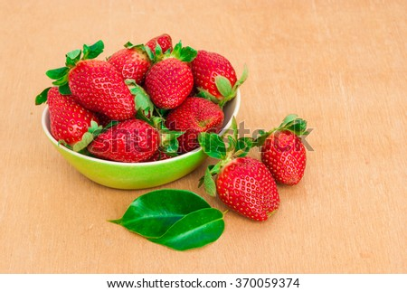 Strawberries. Organic Berries Closeup with mint. Ripe Strawberry In The Fruit Garden, Old Wooden Bowl Filled With Succulent Juicy Fresh Ripe Red Strawberries On An Old Birch Stump. Toned Image  - stock photo