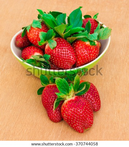 Strawberries. Organic Closeup with mint, natural non GMO rustic style. Ripe Strawberry In Fruit Garden, Old Wooden Bowl Filled With Succulent Juicy Fresh Ripe Red berries On An Old Background - stock photo