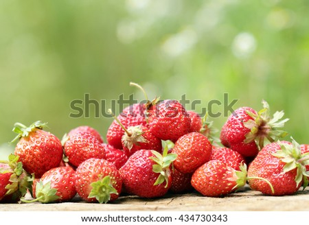strawberries scattered on a wooden surface