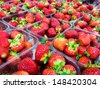 Strawberries with green weed in plastic containers at marketplace - stock photo