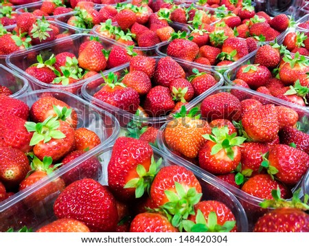 Strawberries with green weed in plastic containers at marketplace