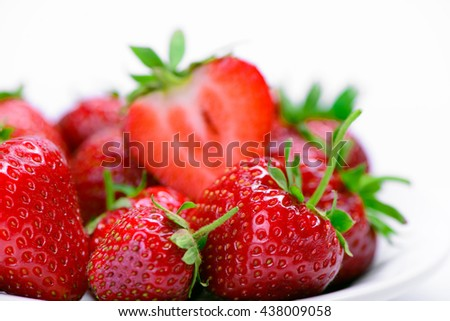 Strawberries with leaves on a white plate