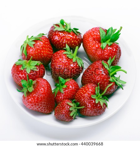 Strawberries with leaves on a white plate - stock photo