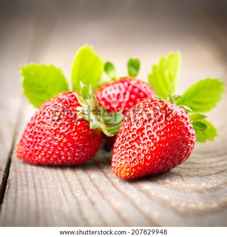 Strawberries with leaves on a wooden table - stock photo