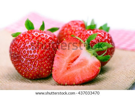 Strawberries with leaves on burlap cloth isolated on a white