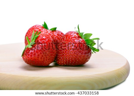 Strawberries with leaves on cutting board isolated on a white background