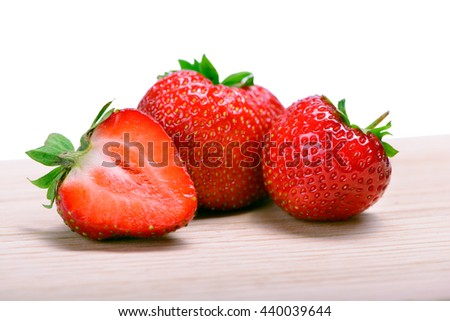 Strawberries with leaves on cutting board isolated on a white background - stock photo
