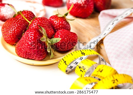 Strawberries with measuring tape on a white background