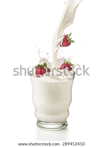 Strawberries with milk poured into a glass with splashes. Isolated on withe background - stock photo