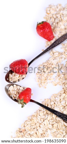 Strawberries with oatmeal and vintage spoons, isolated on white