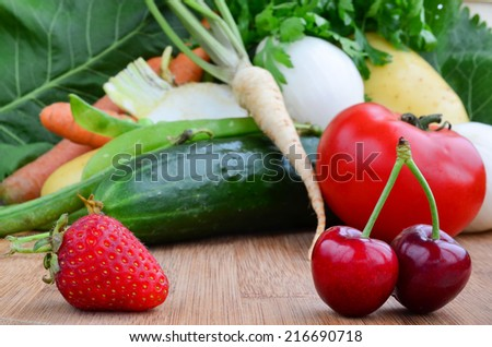 Strawberry and cherries in foreground and vegetables in background, shallow depth of field - stock photo