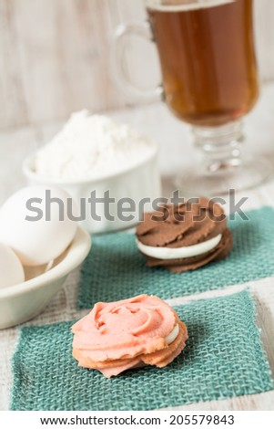 Strawberry and chocolate cookies with cup of tea and flour and eggs