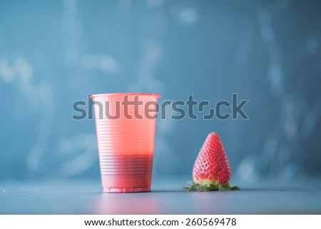 Strawberry and glass of juice on stone background - stock photo