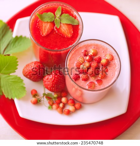 Strawberry and wild strawberry cocktail. Healthy juices. Prepared with fresh fruits. Pieces of fresh fruits. Diet drinks. Presented in glasses and green leaves. - stock photo