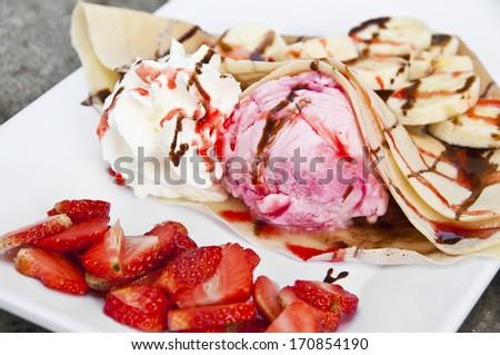 Strawberry banana crape with ice cream. - stock photo