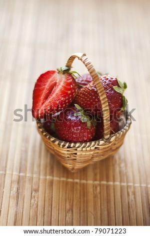 strawberry basket on bamboo background - stock photo