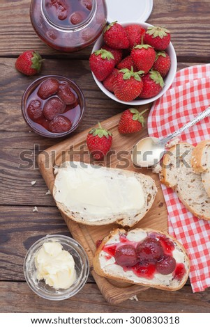 Strawberry berries, Strawberry jam, butter and bread on wooden table. Breakfast with strawberry jam top view vertical. Macro shot selective focus - stock photo