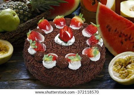 Strawberry birthday cake with whipped cream and chocolate - stock photo