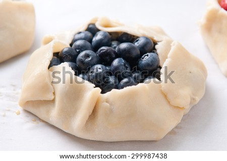 strawberry, blueberry and cherry galettes uncooked, before baking - stock photo