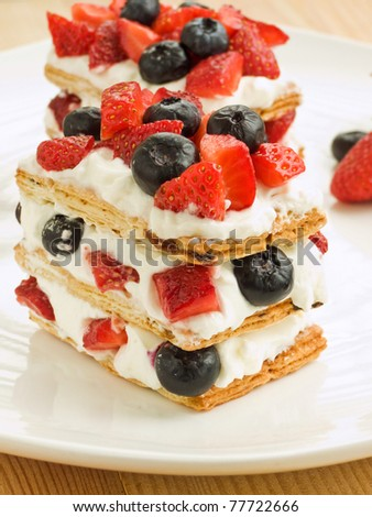 Strawberry-blueberry mille feuille with whipped sour cream. Shallow dof. - stock photo