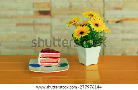 strawberry cake and sun flowers on the yellow wood table - stock photo