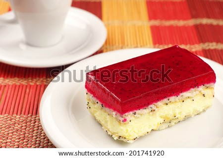 Strawberry cake with poppy and cup of coffee on bamboo napkin