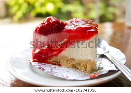 Strawberry cheese cake on wood in coffee shop - stock photo