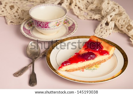 Strawberry cheesecake in pretty setting with teacup and doily