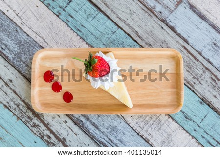 Strawberry Cheesecake on the wood plate on top view (selective focus) - stock photo