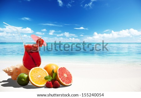 strawberry cocktail and tropical fruit on the beach - stock photo