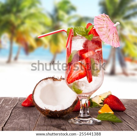 Strawberry cocktail on wooden table with beach background, summer concept, fresh berry fruits - stock photo