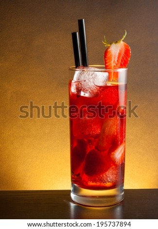 Strawberry cocktail with ice on wood table with space for text and golden gradient background - stock photo