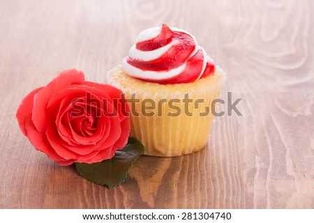 Strawberry cupcake with a beautiful red rose on wooden table, a simple treat to a loved one - stock photo
