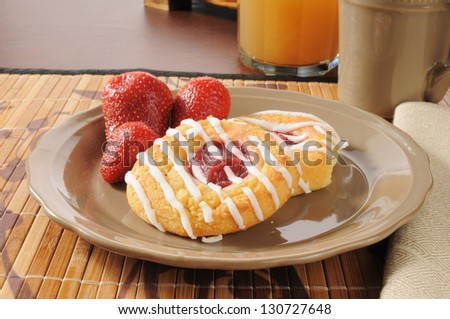 Strawberry danish rolls with unfiltered apple juice and coffee