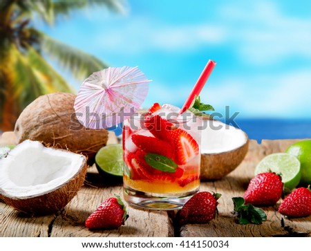 Strawberry drink on wood with blur beach background