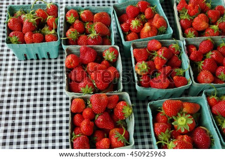 Strawberry filled containers on picnic tablecloth