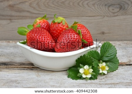Strawberry. Fresh strawberries. Red strawberry on wood background. Red strawberries. Sweet strawberry. Strawberry with green leaves. Healthy strawberries. strawberry flower. Strawberry still life.  - stock photo