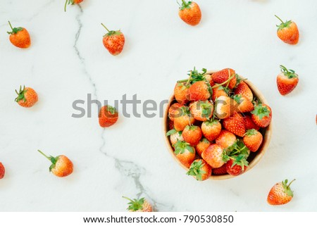 Strawberry fruit in wooden bowl on white stone background