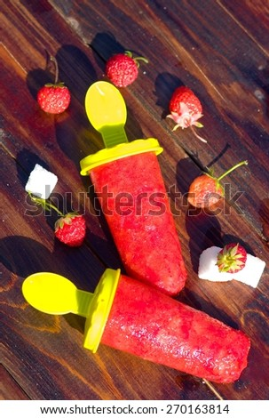 Strawberry homemade Popsicles with berries outdore. Focus on ice - stock photo