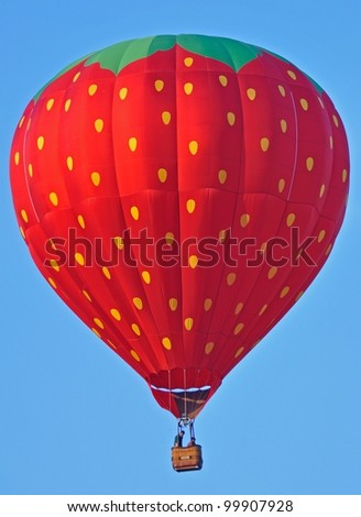 Strawberry hot air balloon in flight with blue sky - stock photo