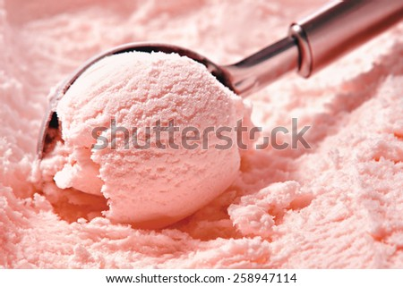 Strawberry ice cream scooped out of container  - stock photo