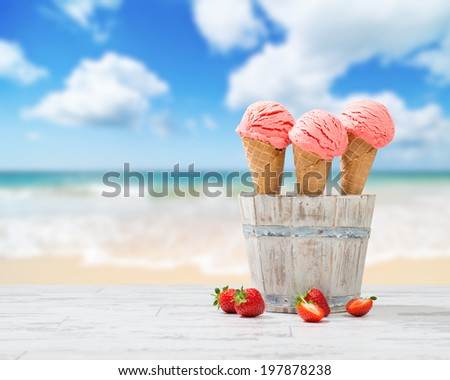 Strawberry ice creams with fruit on wooden decking with beach blur background - stock photo