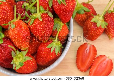 Strawberry in a bowl and set on wooden