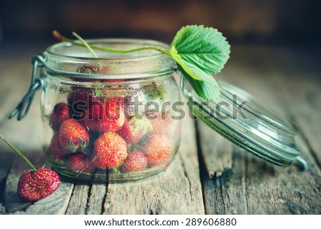 Strawberry in a Tin on Wooden Background. Selective focus. Country style - stock photo