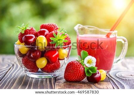 strawberry in bowl and juice  on an old wooden table