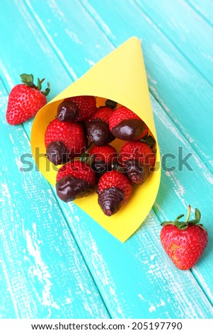 Strawberry in chocolate on skewers in paper bag on table close-up - stock photo