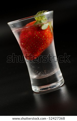 Strawberry in ice in a glass on a black background