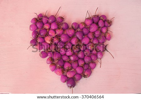 Strawberry in shape of heart on color wooden background  - stock photo