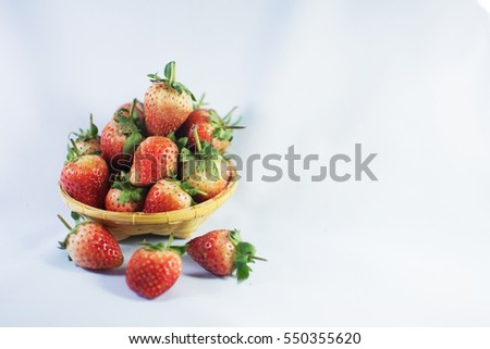 Strawberry in wicker baskets on white background.