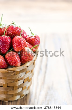Strawberry in wicker baskets on wood table